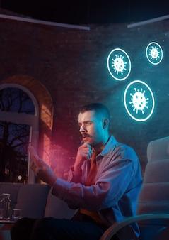 Шокированный, расстроенный и грустный кавказский мужчина использует гаджеты для получения информации о распространении пандемии коронавируса. оставайся дома, чтобы быть в безопасности. анализируем ситуацию с мировым количеством заболевших, здравоохранением, медициной.