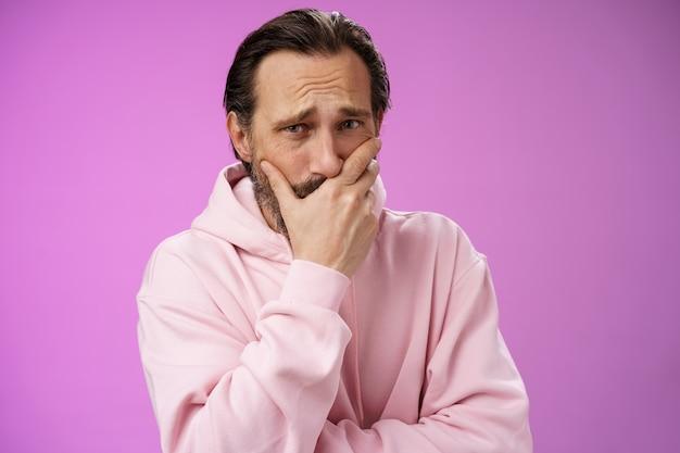 충격을받은 화가 잘 생긴 성숙한 수염 난 남자는 끔찍한 소식을 듣고 슬픔을 표현 공감 헐떡 거리며 손 입 반응을 잃고 울고 울고 감정, 보라색 배경을 제어 할 수 없습니다.