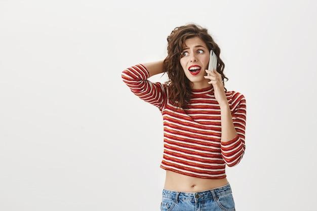 ショックを受けた動揺の女性が電話で悪いニュースを受け取る