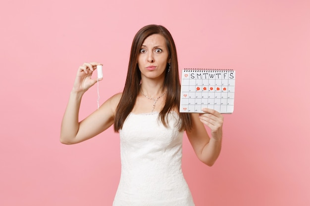 Shocked upset woman in white dress holding tampon, female periods calendar for checking menstruation days