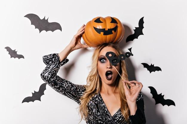 입을 벌리고 포즈를 취하는 진한 화장과 충격을받은 뱀파이어 소녀. 할로윈 액세서리를 들고 마녀 의상에서 매혹적인 금발 여자.
