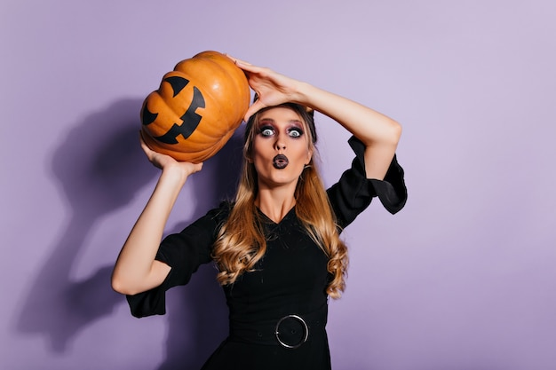 Shocked white witch standing on purple wall with magic pumpkin. indoor photo of gorgeous wizard in black dress.
