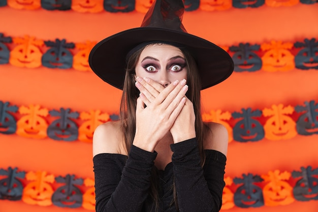 Shocked witch girl in black halloween costume covering her mouth in surprise isolated over orange pumpkin wall