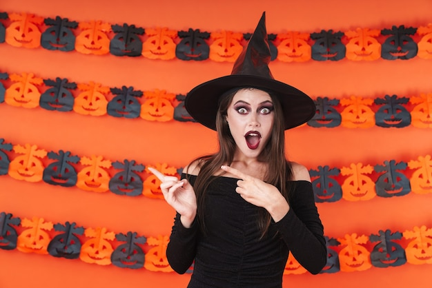 Shocked witch girl in black halloween costume pointing fingers aside at copyspace isolated over orange pumpkin wall
