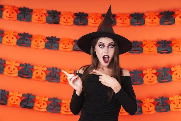주황색 호박 벽 위에 격리된 카피스페이스에서 손가락을 옆으로 가리키는 검은 할로윈 의상을 입은 충격된 마녀 소녀