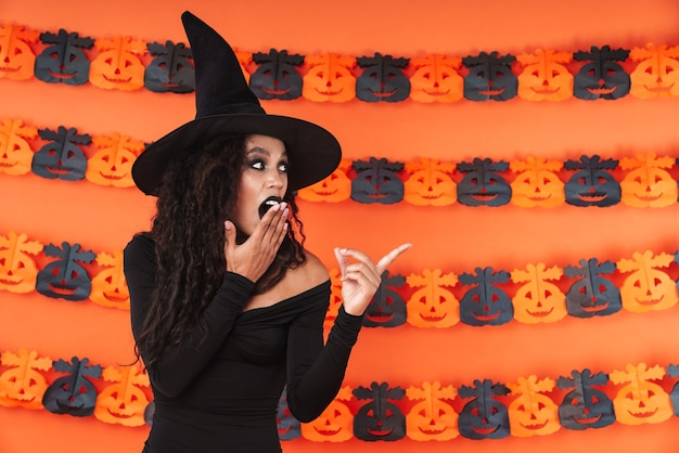 Shocked witch woman in black halloween costume pointing finger aside at copyspace isolated over orange pumpkin wall