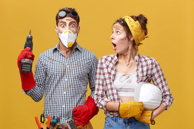 Shocked woman in checkered shirt holding helmet looking at his husband with wide opened mouth who done something wrong. astonished handsome young male in protective mask holding drilling machine