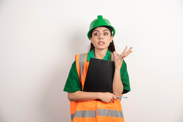 Shocked woman constructor wearing green helmet standing with clipboard . high quality photo