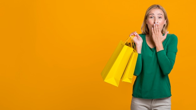 Shocked woman covering her mouth while holding many shopping bags with copy space
