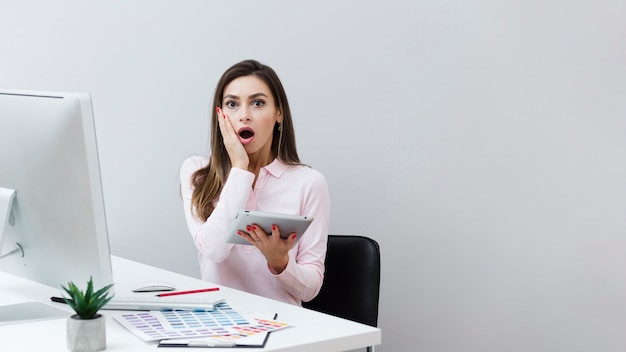 Shocked woman at desk holding tablet