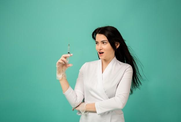 Шокированная женщина-врач в белом костюме держит медицинский шприц на бирюзе