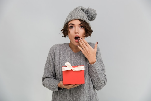 Shocked woman dressed in sweater and warm hat holding gift.