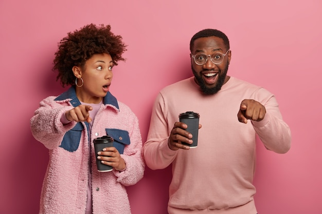 Shocked woman and happy man point at camera, notice something incredible, drink coffee from disposable cups, wear stylish outfit, express different emotions