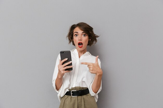 灰色の壁に隔離された携帯電話を持って使用してショックを受けた