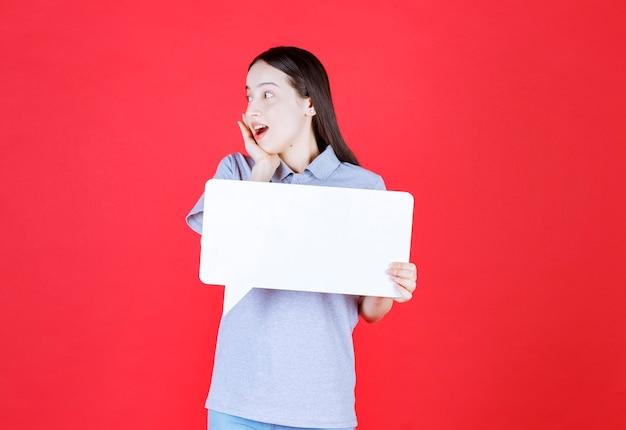 Шокированная женщина держит доску и смотрит в сторону