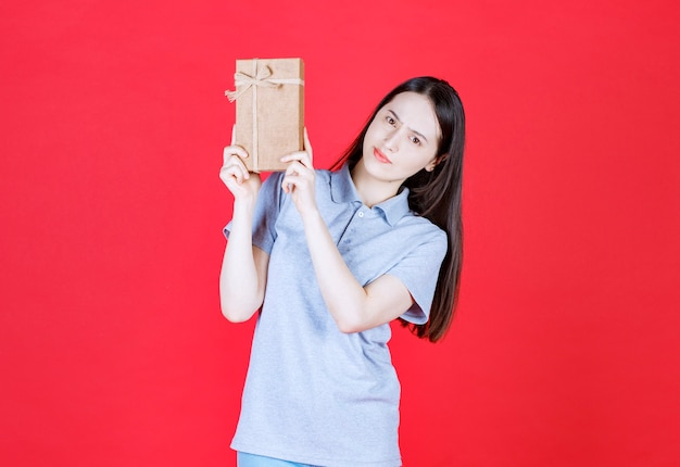Shocked woman holding gift box and looking at front