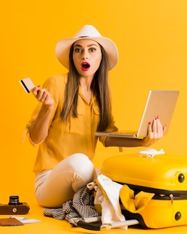 Shocked woman holding laptop and credit card with luggage next to her