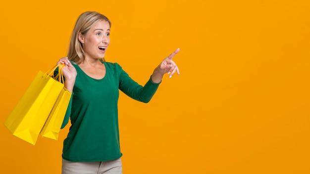 Donna scossa che tiene molte borse della spesa e che indica al possibile negozio