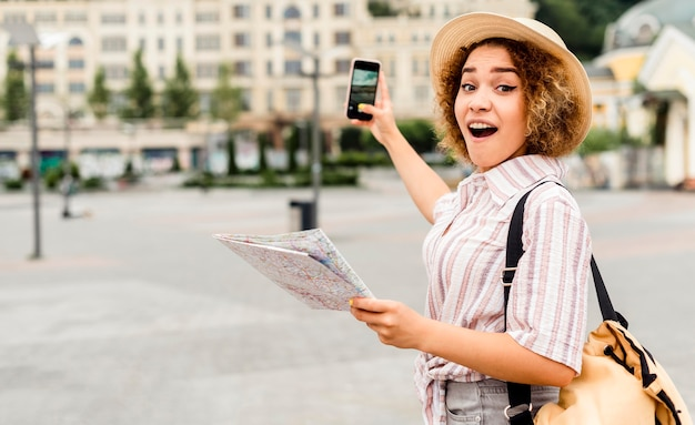 Shocked woman holding a map and a phone