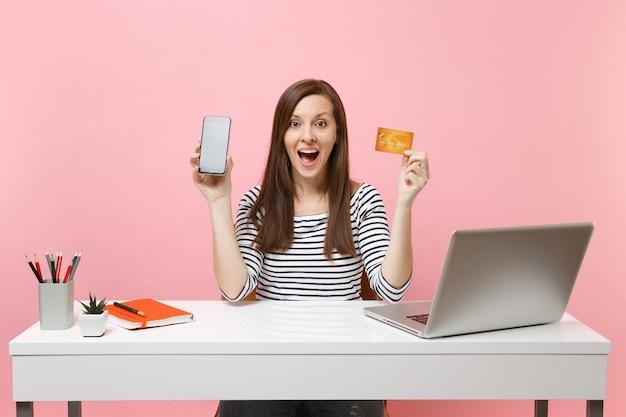 Потрясенная женщина, держащая мобильный телефон с пустым пустым экраном, кредитная карта сидит за белым столом с современным портативным компьютером, изолированным на пастельно-розовом фоне. достижение деловой карьеры. скопируйте пространство.
