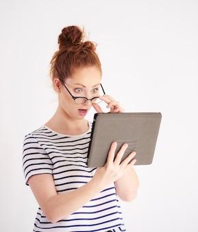 Donna scioccata in possesso di un tablet shot