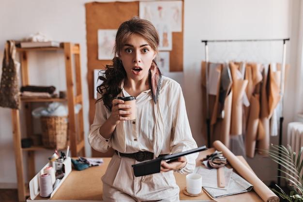 ショックを受けた女性はコーヒーカップとコンピューターのタブレットを保持します