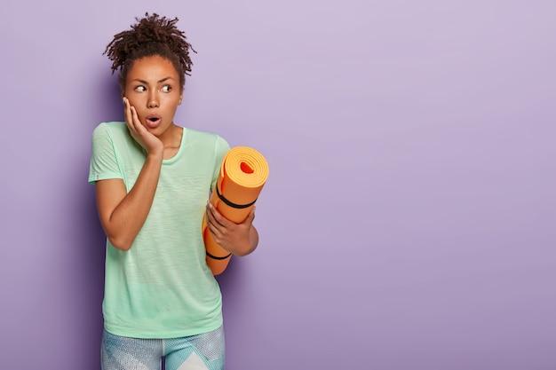 Шокированная женщина держит коврик для йоги