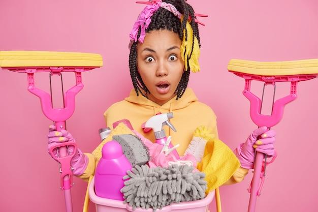 Шокированная женщина-домработница делает генеральную уборку дома в толстовке с капюшоном и держит две швабры