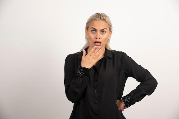 Шокированная женщина в черной рубашке позирует на белом фоне. фото высокого качества