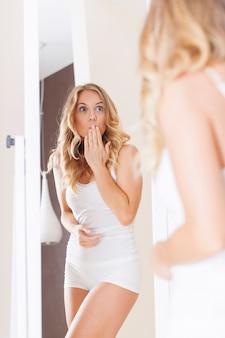 鏡の前でショックを受けた女性