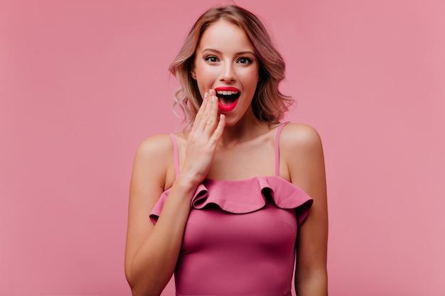 Шокированная женщина в хорошем настроении с красивым макияжем и яркими губами позирует перед камерой, демонстрируя удивление
