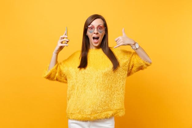 心臓の眼鏡をかけたショックを受けた女性は、携帯電話を持って次のように電話のジェスチャーをします。手で私に電話をかけ直し、明るい黄色の背景で隔離された電話で話しているような指。コミュニケーションの概念。
