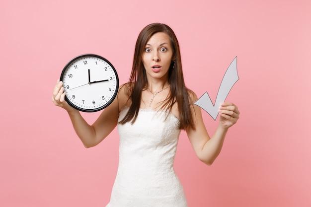Шокированная женщина в кружевном белом платье держит галочку и круглый будильник