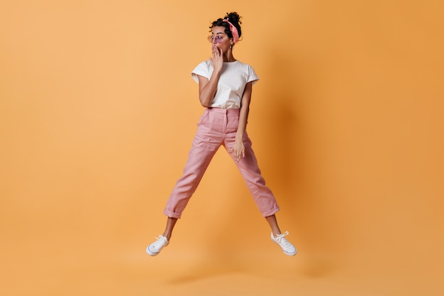 Шокированная женщина в розовых штанах прыгает и смотрит в сторону