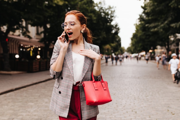 電話で話している格子縞のジャケットのショックを受けた女性