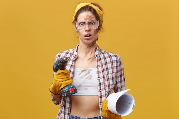 Шокированная женщина в защитных перчатках, клетчатой рубашке и желтой повязке на голове, держащая дрель и свернутую бумагу, с грязным лицом ремонтирует в помещении, удивленная, увидев, сколько ей нужно сделать