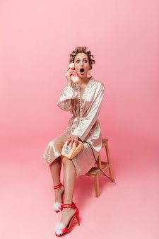 실크 가운에 충격을받은 여자가 전화로 이야기하고 놀람 앞에서보고 의자에 앉아있다.