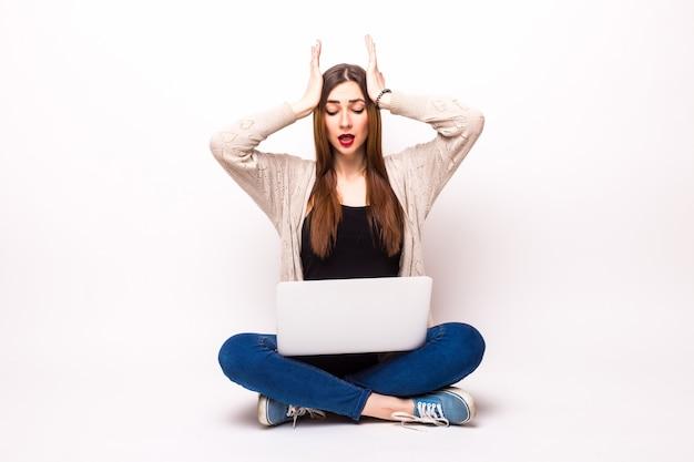 Шокированная женщина в футболке и очках сидит на полу с портативным компьютером и смотрит в камеру над серым