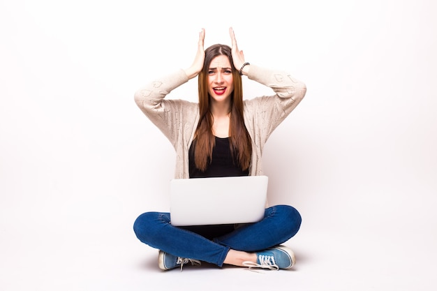 ラップトップコンピューターで床に座って、灰色の上にカメラを見ているtシャツと眼鏡のショックを受けた女性
