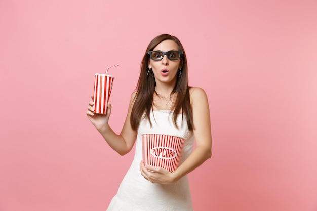 흰 드레스에 충격을받은 여자, 팝콘 양동이를 들고 영화 필름을 보는 3d 안경, 소다 또는 콜라의 플라스틱 컵