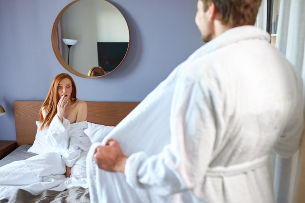Shocked woman look at man in bathrobe