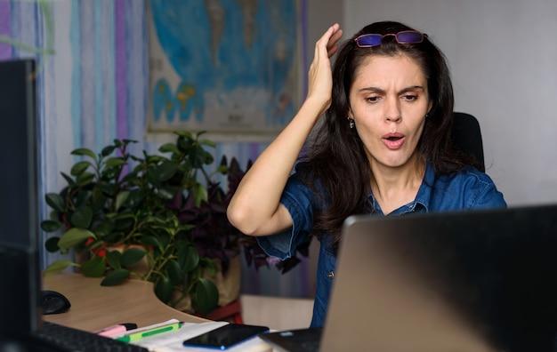 Шокирован женщина смотрит на экран ноутбука