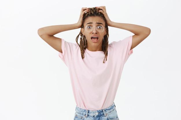 Шокированная женщина выглядит неуверенно, в панике и тревожно хватается за голову