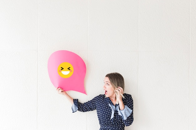 Shocked woman looking at speech bubble paper showing laughing icon