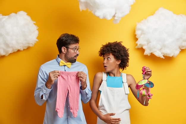Shocked woman and man stare at each other with embarrassement, come to training lesson for future parents, pose with mobile and babys clothes, are not prepared for parenthood. child birth concept