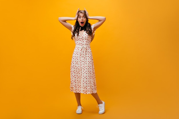Shocked woman in midi dress looks into camera. curly girl in white summer outfit and sneakers posing on orange background.