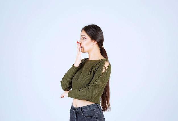 Una modella scioccata in piedi e che copre la bocca con una mano.