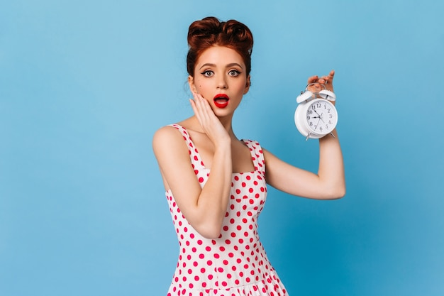 Shocked woman in polka-dot dress holding clock. amazed ginger pinup lady showing time on blue space.