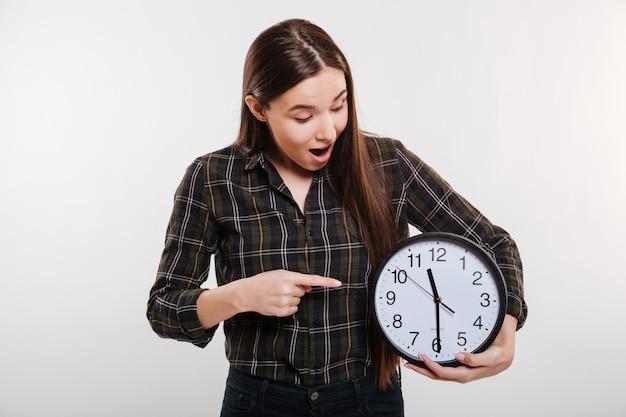 Donna scossa in camicia che tiene l'orologio