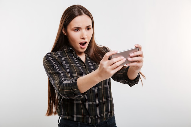 Shocked woman in shirt playing on phone